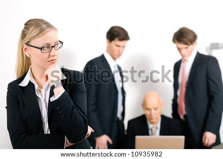 Thinking business woman standing in front of her colleagues; selective focus on woman