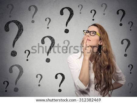 Thinking business woman with glasses looking up on many questions mark isolated on gray wall background Stock photo ©
