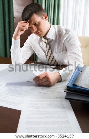 Thinking businessman touching his head holding a document sitting at the table