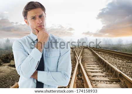 Thinking businessman with hand on chin against railway tracks leading to misty forest