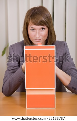 thinking businesswoman with file card holder in office