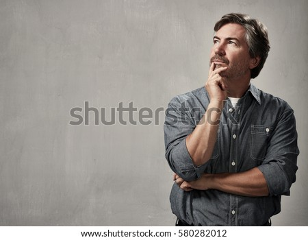 Thinking caucasian man portrait over gray wall background
