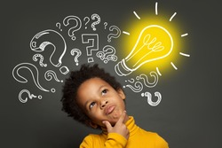 Thinking child boy on black background with light bulb and question marks. Brainstorming and idea concept