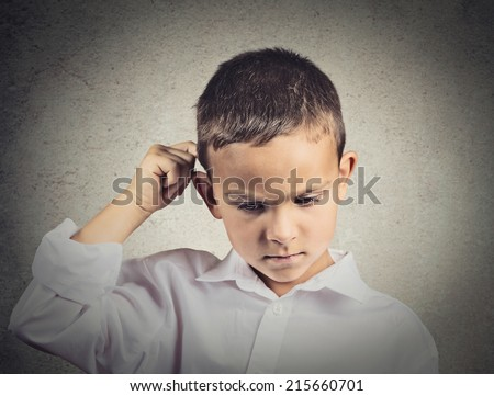 Thinking child, scratching back of his head isolated grey wall background. Human face expressions, emotions, body language