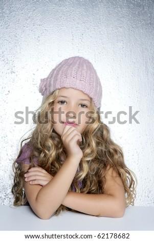 Thinking gesture little girl winter pink cap portrait silver background