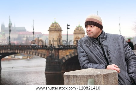 Thinking man looking on Prague bridge spring background under blue sky
