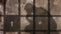 Thinking man Shadow Under Jail Bars.