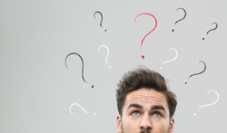 thinking man with many question marks above his head, against grey background