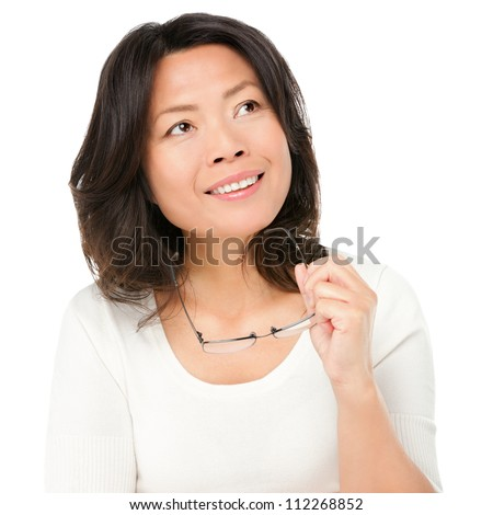 Thinking mature asian woman holding glasses eyewear looking up to the side at copy space. Asian Chinese mature woman isolated on white background in studio.