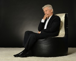 Thinking mature businessman sitting in armchair on black background