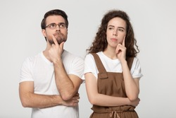Thinking millennial couple pose isolated on grey studio background, pretty girl handsome guy wearing glasses touch chin posture of indecision doubting feelings anxiety, deliberating brain work concept