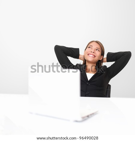 Thinking office worker day dreaming looking up smiling happy. Young business woman in suit sitting at office desk with laptop. Young mixed race Asian / Caucasian businesswoman.