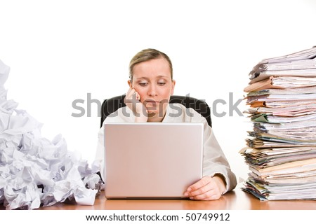 Thinking or tired businesswoman with stack of paperwork, pile of crumpled papers and a laptop computer.