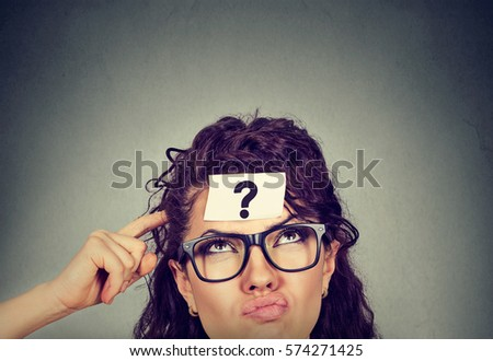 Thinking perplexed woman with question mark isolated on gray wall background. Thoughtful girl scratching head looking up solving a problem  #574271425