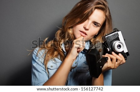 Thinking photographer woman holding old camera