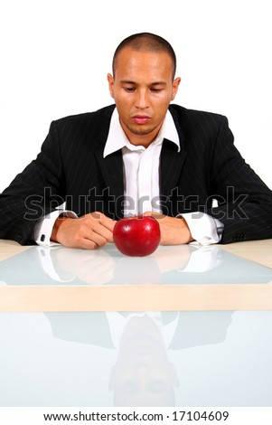 Thinking Process Young businessman sitting in front of a red apple thinking. Isolate over white. The table mirrors the image creating a nice effect!
