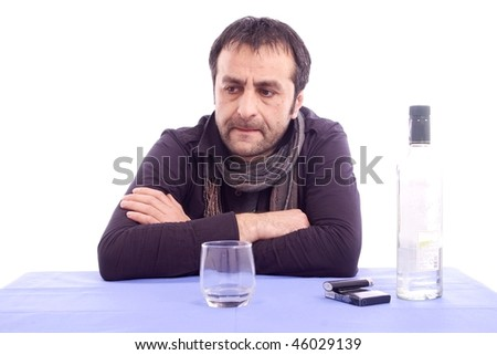 Thinking sad looking man sitting at the table isolated on white background