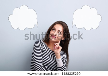Thinking smiling young woman looking up on two empty choice bubble above on blue background with empty copy space