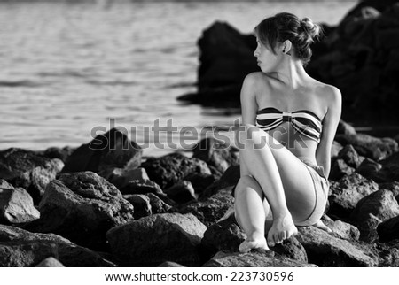 Thinking woman on the rocks near the sea black and white
