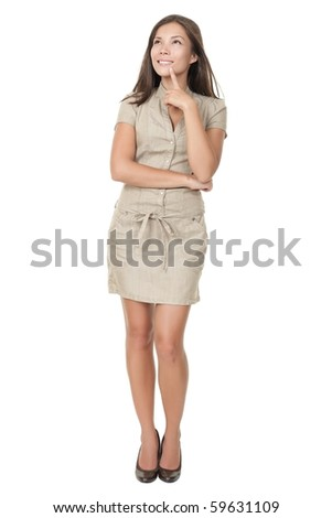 Thinking woman standing in full length isolated on white background in beige neutral dress. Mixed asian / caucasian young woman.