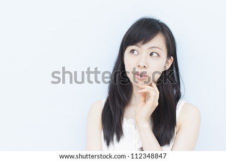 thinking woman thinking, against pale blue background