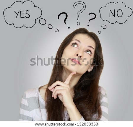 Thinking young woman with yes or no choice looking up with finger at face on grey background