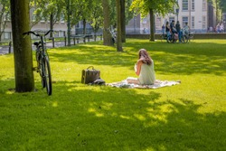 Thinly dressed unknown young woman sitting on a plaid in the grass looks in the Dutch park on her smartphone. Her bike is parked against a tree. In the background a few teenagers are talking.