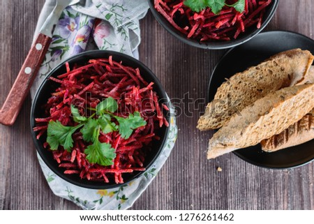 Thinly sliced ​​fresh beets in a black salad bowl with sprigs of cilantro ready for eating are on a wooden table. Shredded beet salad, closeup.
