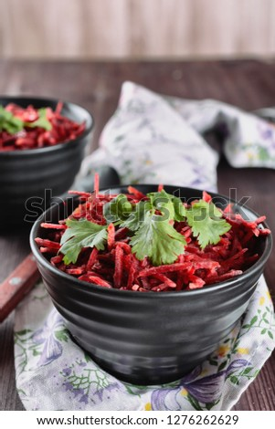 Thinly sliced ​​fresh beets in a black salad bowl with sprigs of cilantro ready for eating are on a wooden table. Shredded beet salad, closeup, vertical orientation.
