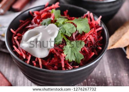 Thinly sliced ​​fresh beets in a black salad bowl with sprigs of cilantro ready for eating are on a wooden table. Thinly shredded beet salad.