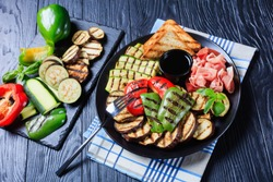 thinly sliced prosciutto ham served with grilled sweet pepper, zucchini slices, eggplants, toasts on a black plate with vinegar sauce. ingredients on a slate tray