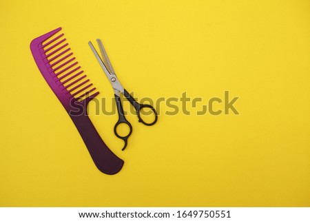 thinning scissors and a purple comb for hair on a yellow background, space for text. Barber Tools. flat lay