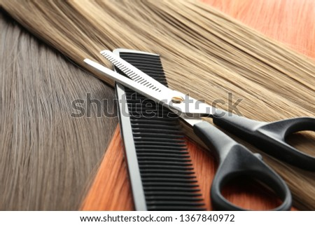 Thinning scissors and comb on hair, closeup. Hairdresser service
