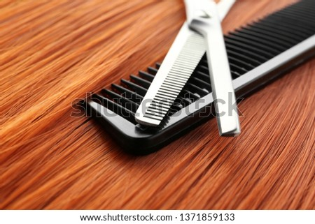 Thinning scissors and comb on red hair, closeup. Hairdresser service