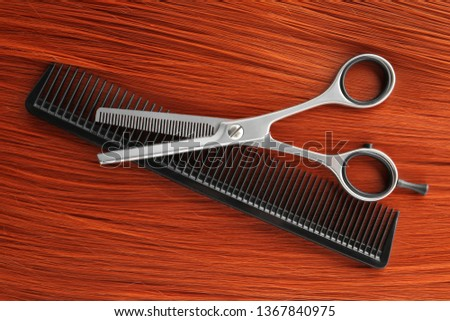 Thinning scissors and comb on red hair, top view. Hairdresser service