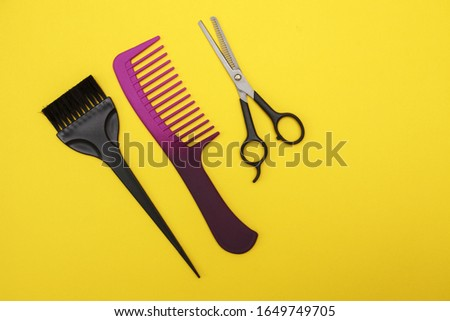 thinning scissors, comb and hair brush on a yellow background, space for text. Barber Tools. flat lay