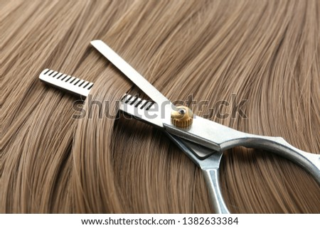 Thinning scissors on light brown hair, closeup. Hairdresser service
