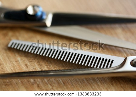 Thinning shears lie on wooden table in hair salon closeup. Stylish hairstyle concept background.