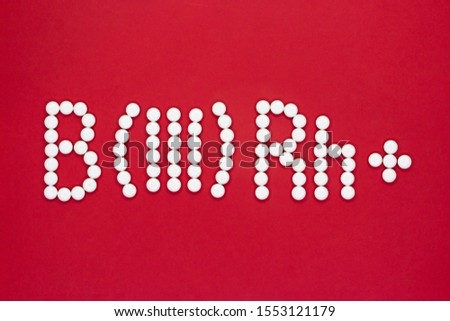 Third blood type. Blood type symbol from white pills on a red background. Blood type treatment.
