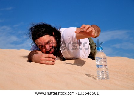 Thirst man in the desert take plastic bottle with water - stock photo