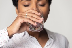 Thirsty African American girl with closed eyes drinking clean mineral water close up, young woman holding glass, healthy lifestyle concept, natural beauty, isolated on grey studio background