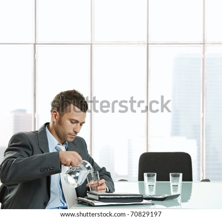 Thirsty businessman sitting at meeting table pouring water from jug into glass to drink in meeting break.