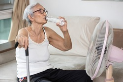 Thirsty elderly woman drinking water to quench thirst,refresh in hot summer weather,senior grandmother enjoying cooling wind from fan and drink water,keeping body water balance,stay at home,lifestyle