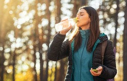 Thirsty girl drinking water in sun lights, hiking by forest, copy space