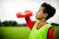 Thirsty junior football player drinking water