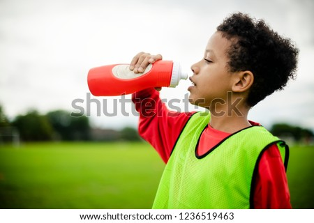 Thirsty junior football player drinking water