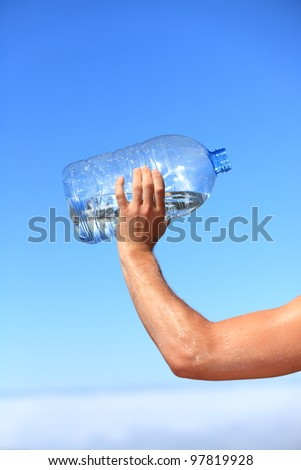 Thirsty man drinking water of big bottle. Closeup of hand holding bottle. Thirst concept image from outdoors on blue sky above the clouds.