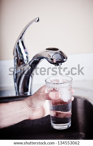 Thirsty man filling a glass of water
