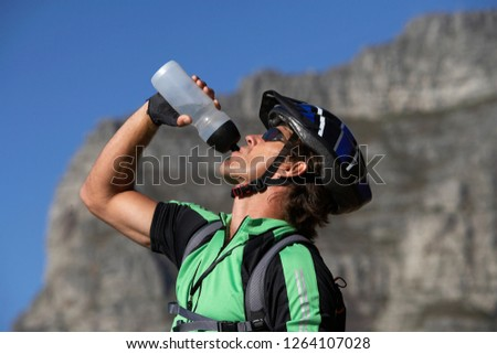 Thirsty man on mountain bike drinking water from bottle on active vacation in profile