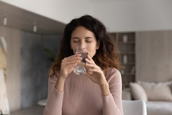 Thirsty millennial Latino woman feel dehydrated drink clean clear mineral still water from glass. Young Hispanic female enjoy pure aqua for body refreshment. Healthy lifestyle, hydration concept.